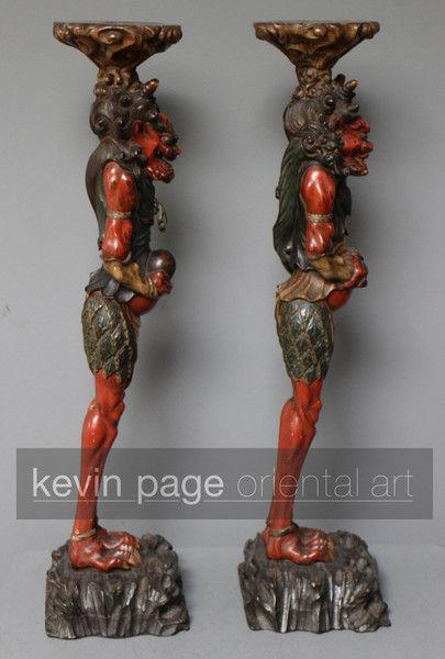 A pair of unusual japanese carved wood candlestick holders in the form of oni