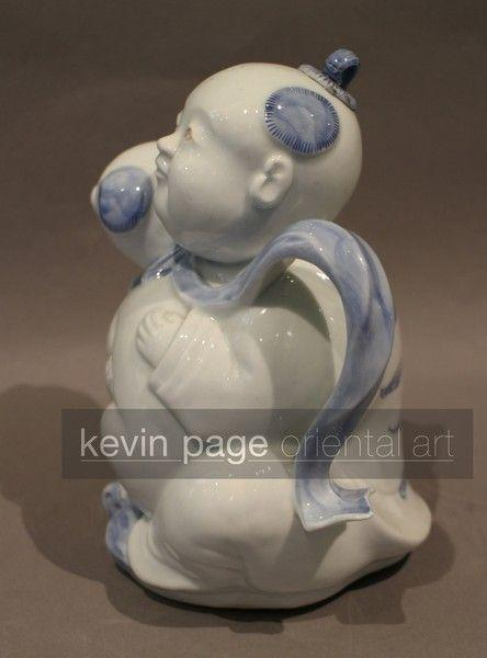 A japanese hirado teapot in the form of a boy with a dog