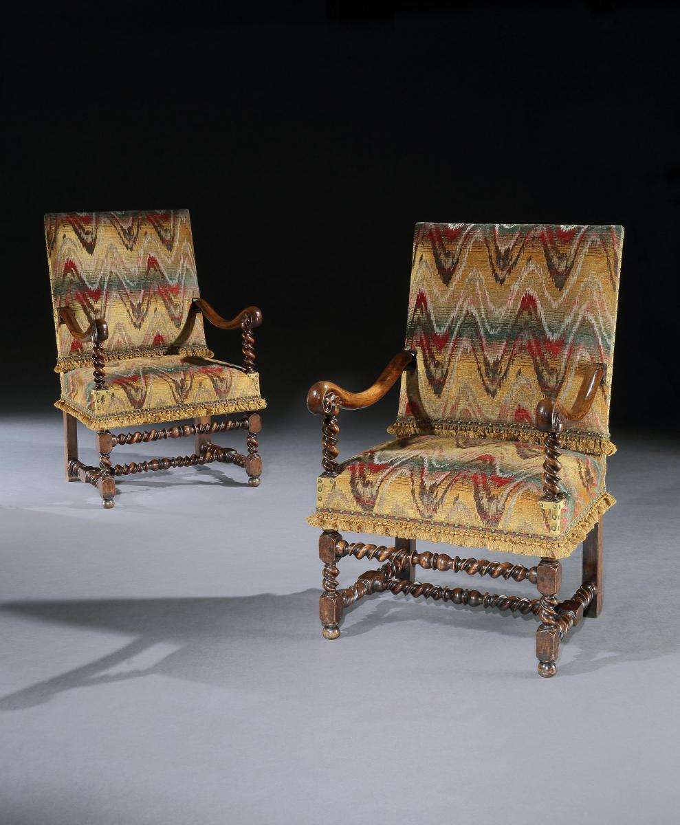 A pair of Flemish, mid-17th century, walnut, open armchairs upholstered in a re-created bargello with custom-made passmenterie