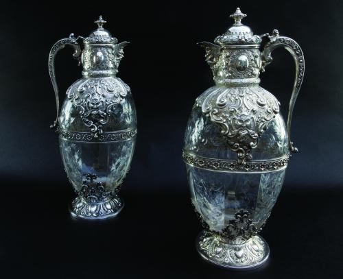 A superb pair of silver-mounted carved crystal claret jugs by Charles Edwards