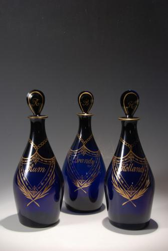 A superb set of three club-shaped blue spirit decanters with rare shield-shaped labels for Rum, Brandy and Hollands.