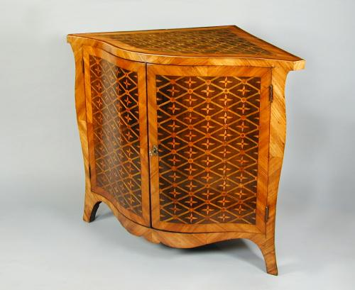 An unusual George III serpentine corner cabinet in harewood with various inlays in the style of Pierre Langlois, c.1775