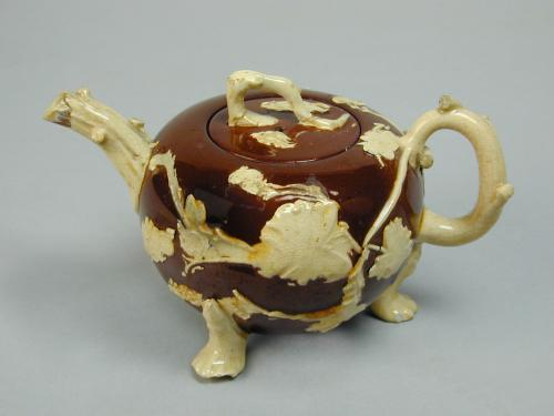 An unusual Staffordshire brown glazed teapot with applied decoration, c.1740