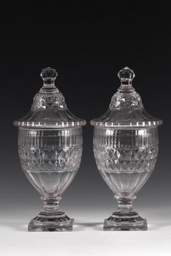 A pair of covered urns cut with bands of diamonds and narrow flutes, on square pedestal feet.  Voneche c. 1800  Height 28.3 cm