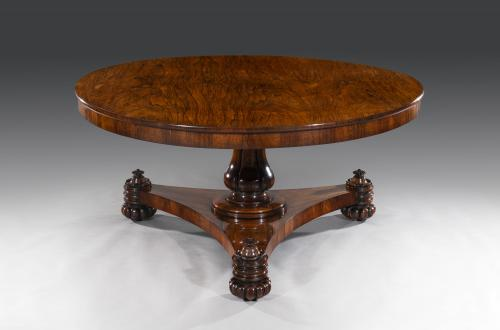 The rosewood veneered tilt-top table is 5' in size. The frieze is cross-banded in rosewood and the carcass is mahogany. The tale