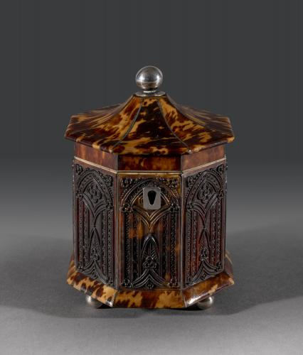 The small octagonal tortoiseshell caddy has a silver ball finial and escutcheon with octagonal pressed gothic arches to each sid