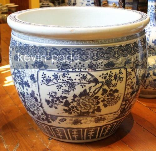 A large antique chinese blue and white jardinière planter decorated with flowers