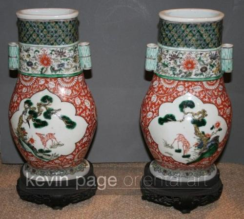 A pair of red ground famille verte vases on original stands