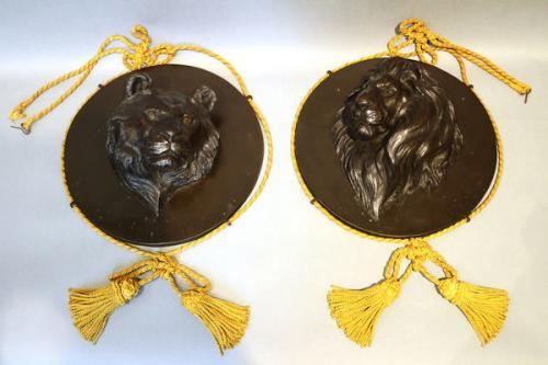 A pair of 19th century japanese bronze lion and tiger head plaques