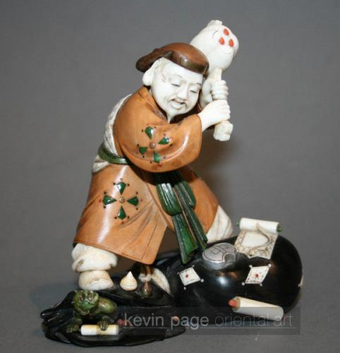 an ivory figure of daikoku with hammer raised to a small green oni in a sack