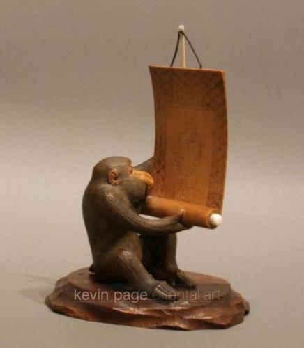 A wood carving of a monkey with a scroll