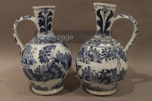 A pair of japanese blue and white jugs decorated with figures in a landscape