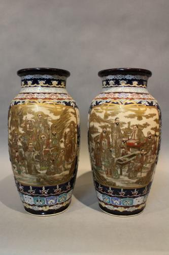 A pair of 19th century japanese satsuma vases decorated with deities and scholars