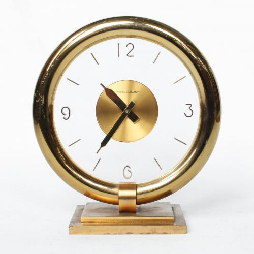 An Art Deco, Jaeger Le Coultre desk clock with innovative case construction of round glass face with optical impression of a fre