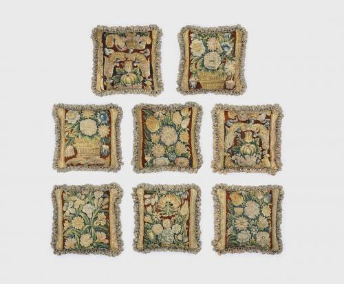 A rare set of eight, mid-17th century, verdure tapestry cushions with custom-made passmenterie