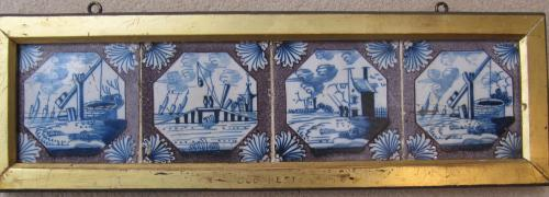A set of four 18th century, English manganese delftware tiles in a gilt frame
