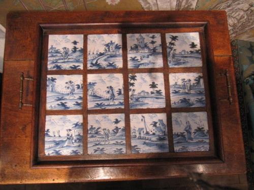 A set of twelve, 18th century, delftware tiles, unusually, made into an oak tray, probably during the early-20th century