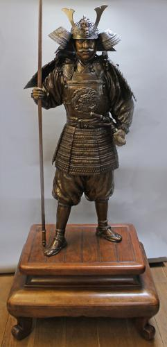 A near life size bronze sculpture of a Samurai with Shibuichi and shakudo inlaid eyes