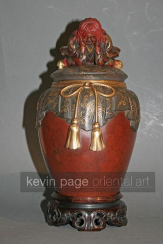 A red lacquer jar and cover with shojo sitting on the top