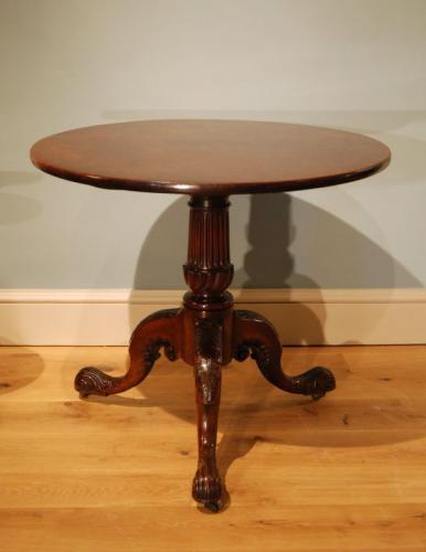 A carved mahogany tripod table of bold form.
