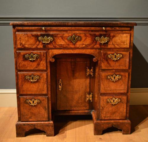 A George II veneered walnut kneehole desk