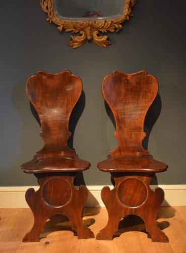 A fine pair of mahogany hall chairs of Scabello form with dished backs