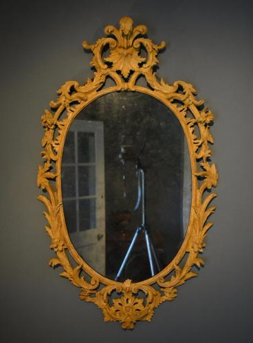 A George III carved oval ochre painted pine mirror