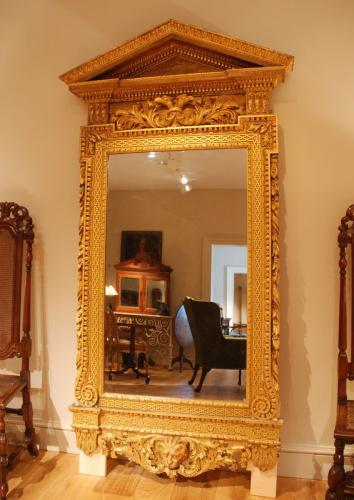 A fine carved giltwood architectural mirror in the Kentian manner