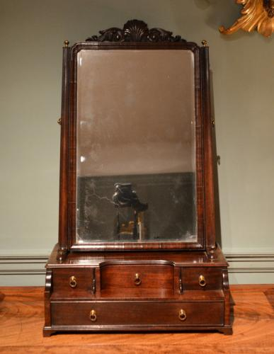 A high quality George II mahogany box toilet mirror having the rare feature of a carved cresting.
