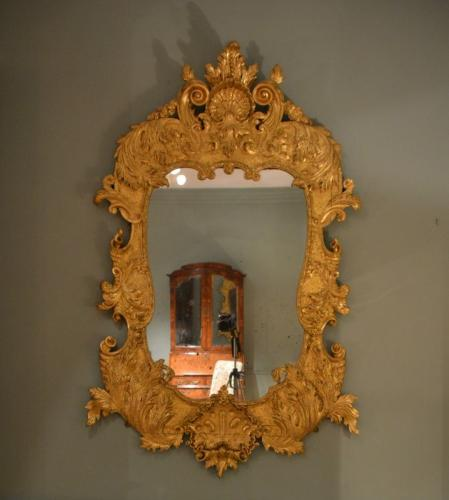 An 18th Century carved gilt wood mirror  This mirror is en suite with table