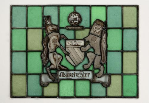 A stained & painted glass panel depicting the Coat of Arms of the City of Manchester