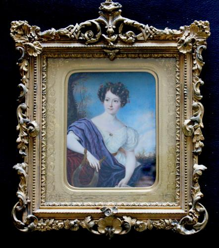 A Regency portrait miniature of a young Lady holding some sheet music with lyre