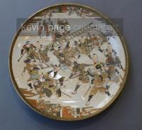 a japanese satsuma plate decorated with a man fighting with a ladder